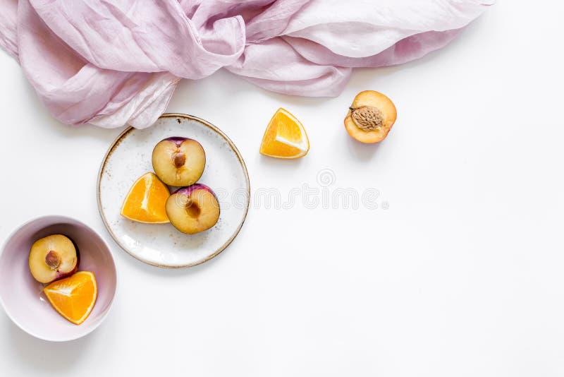 Servet, besnoeiingsperzik en sinaasappel voor exotisch fruit op wit achtergrond hoogste meningsmodel stock fotografie