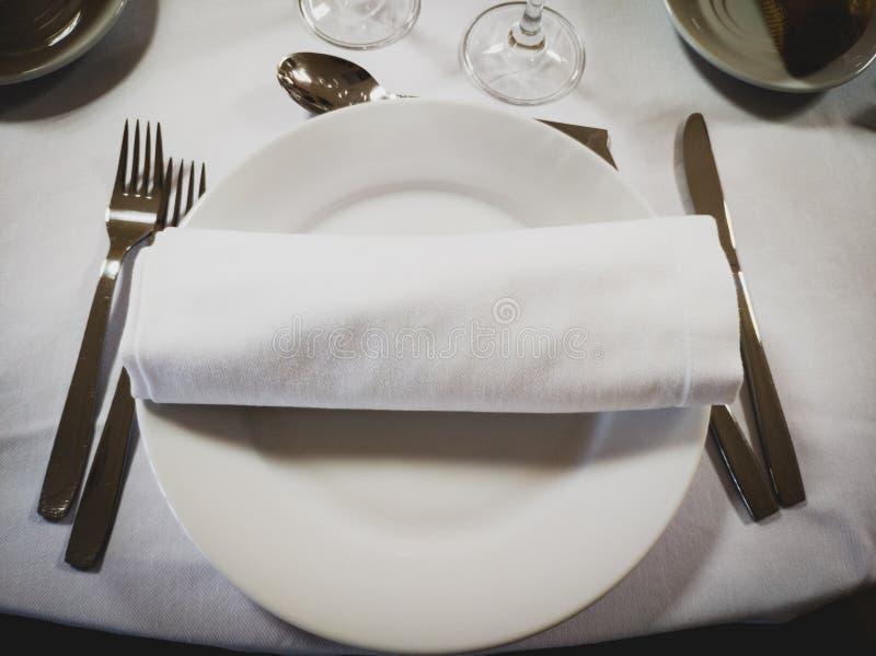 Servet op een lege ronde witte plaat met bestek aan de kanten stock afbeelding