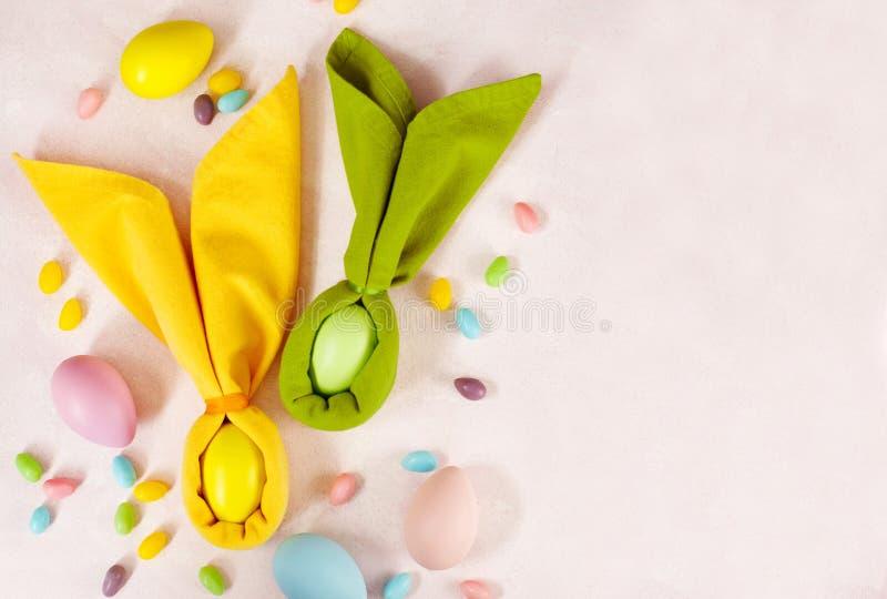 Servetpaashaas, decoratieeieren en Pasen-suikergoed op roze achtergrond stock foto's