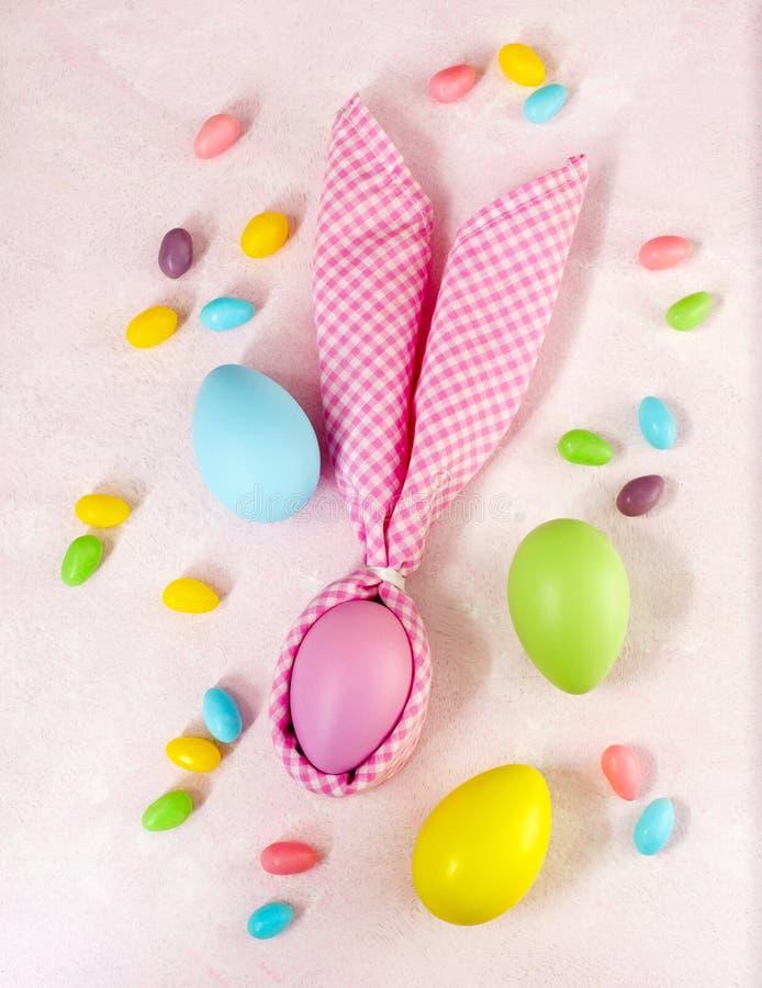Servetpaashaas, decoratieeieren en Pasen-suikergoed op roze achtergrond royalty-vrije stock foto