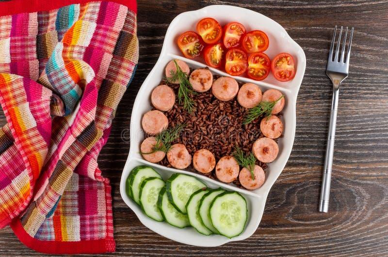 Servett delad maträtt med stekte korvar, röda ris, gurkor, tomat, gaffel på tabellen Top beskådar royaltyfri fotografi