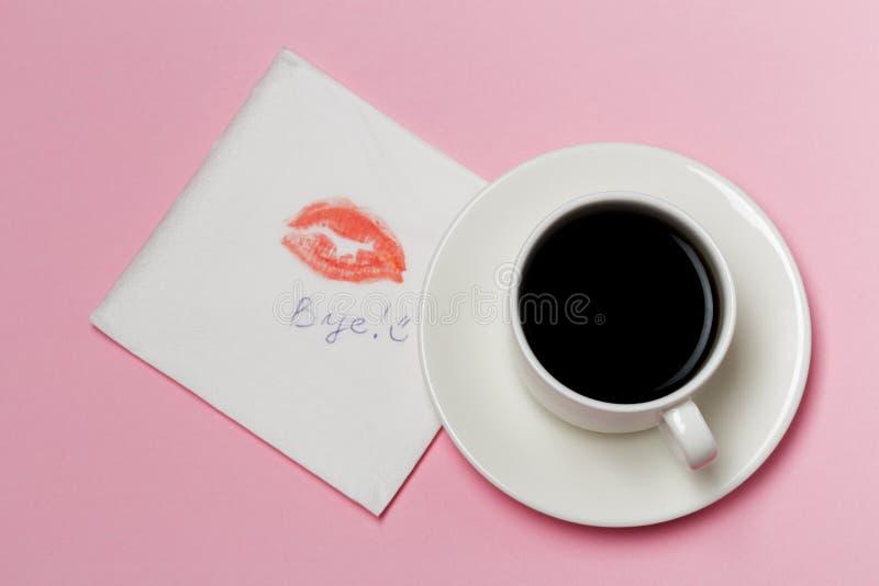 Servett med en kyss- och kaffekopp på rosa bakgrund arkivbilder