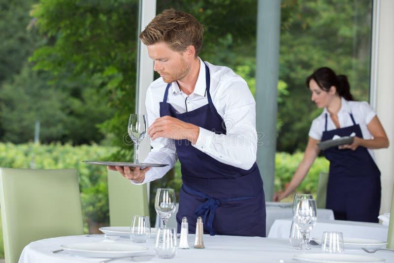 Serveur arrangeant des roses dans le vase sur épouser la table photographie stock