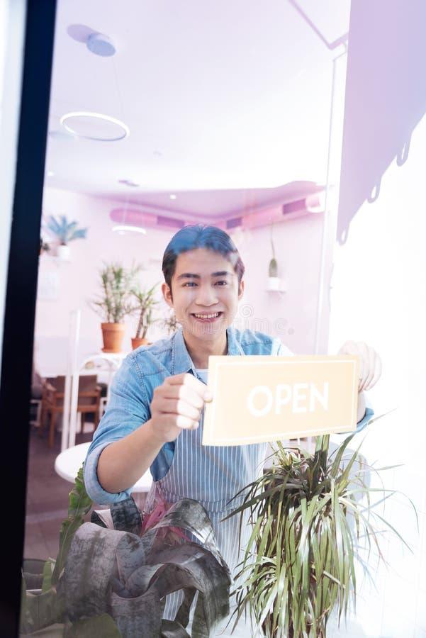 Serveur aux cheveux foncés agréable tenant le filon-couche proche de fenêtre en café photo libre de droits
