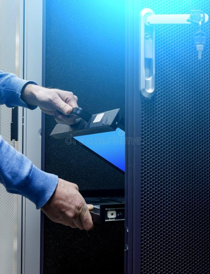 Serveur de moniteur système plié par hommes de mains au centre de traitement des données moderne Lumi photos stock