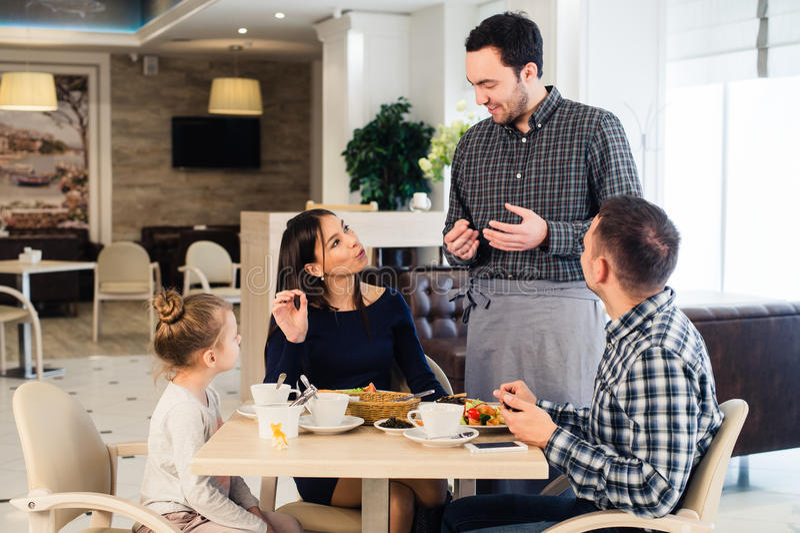 Serveur de sourire amical prenant l'ordre à la table de la famille dînant ensemble images libres de droits