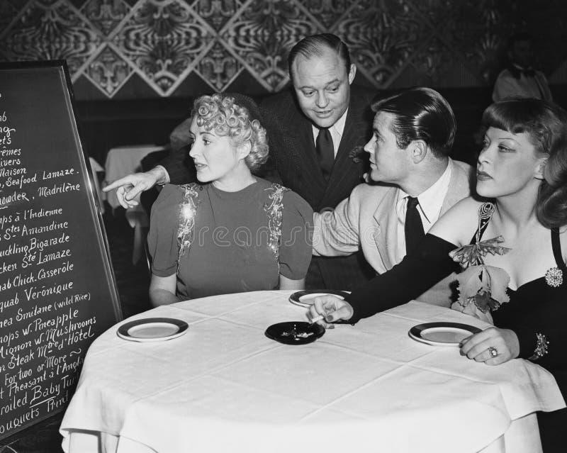 Serveur et clients dans le restaurant (toutes les personnes représentées ne sont pas plus long vivantes et aucun domaine n'existe photo stock