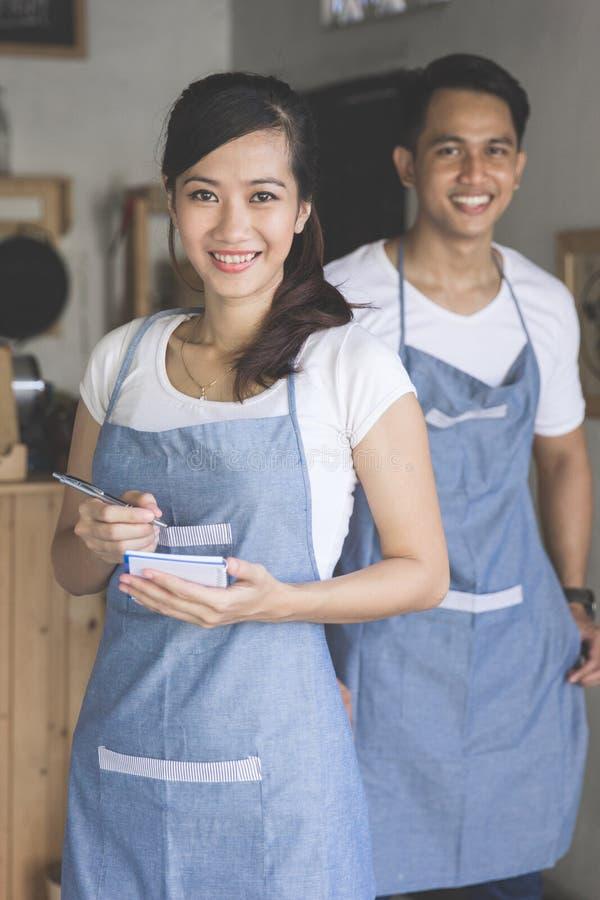 Serveur féminin asiatique dans l'ordre d'écriture de tablier photos stock
