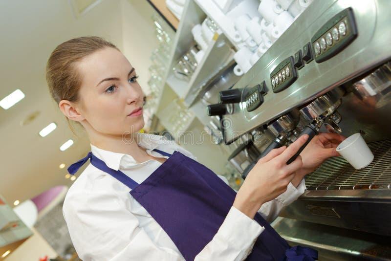 Serveur féminin de barman dans l'uniforme faisant le café à la barre image stock