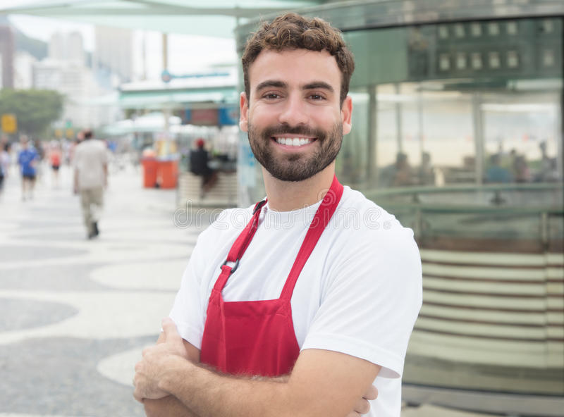 Serveur heureux avec la barbe devant un restaurant photographie stock
