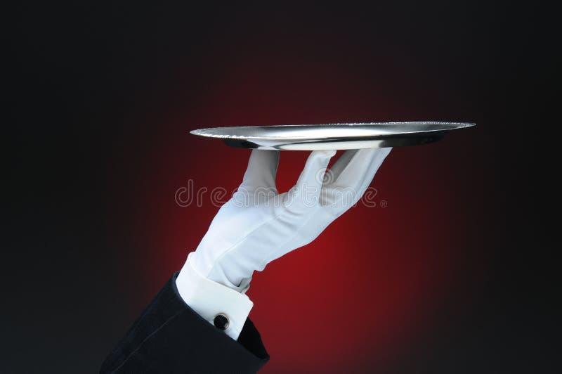 Serveur Holding un plateau argenté de portion dans ses bouts du doigt photo libre de droits