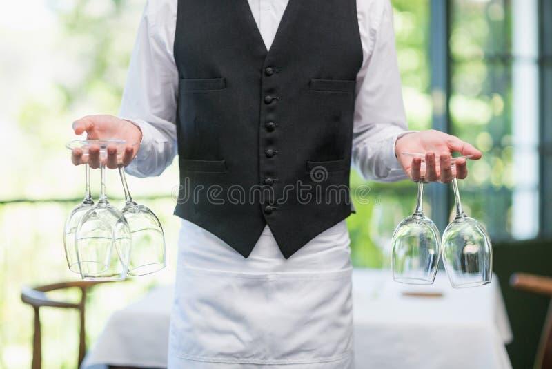 Serveur masculin tenant des verres de vin dans le restaurant photographie stock