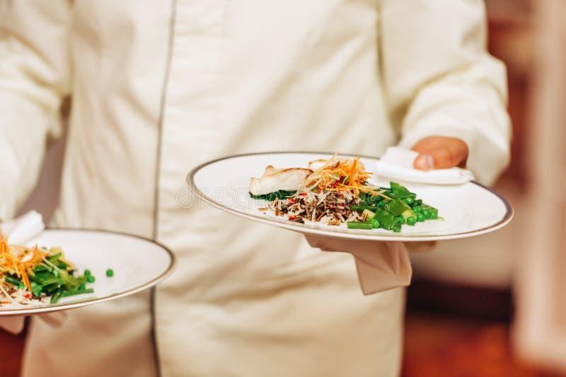 Serveur portant deux plats avec le plat de poissons et de riz sur un certain événement de fête photo stock