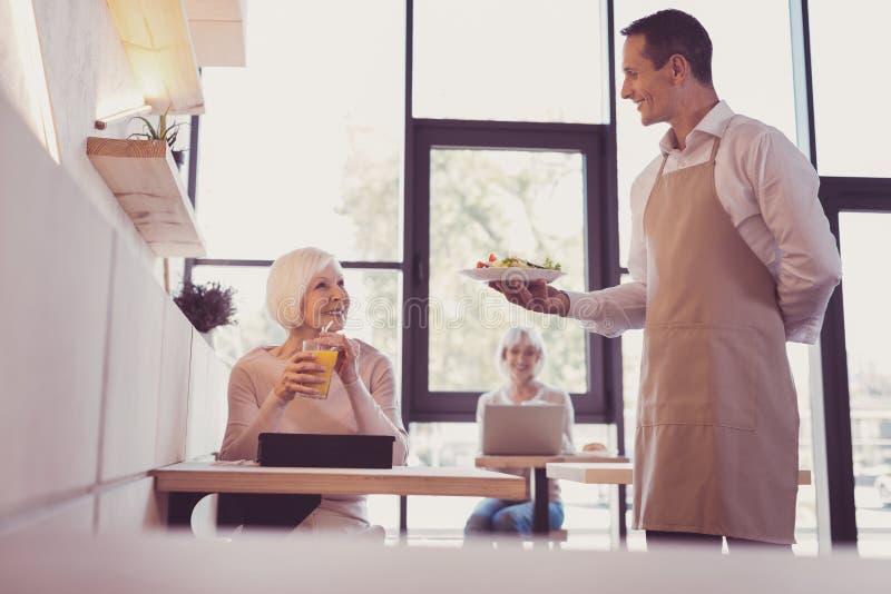 Serveur responsable agréable tenant un plat et un sourire photo stock