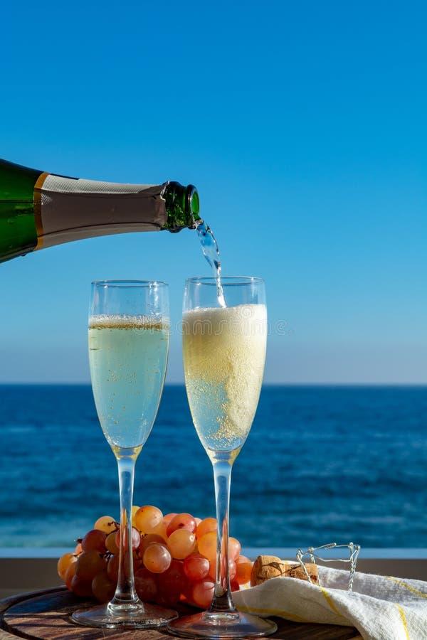 Serveur versant Champagne, prosecco ou cave en deux verres sur la terrasse extérieure avec la vue de mer photos stock