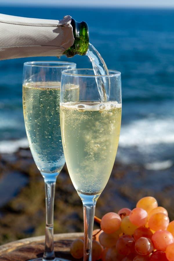Serveur versant Champagne, prosecco ou cave en deux verres sur la terrasse extérieure avec la vue de mer image stock