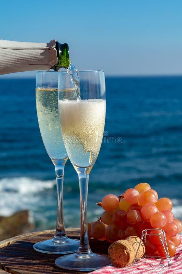 Serveur versant Champagne, prosecco ou cave en deux verres sur la terrasse extérieure avec la vue de mer photo stock