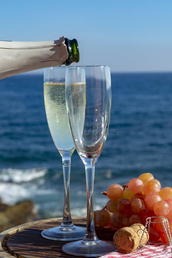 Serveur versant Champagne, prosecco ou cave en deux verres sur la terrasse ext?rieure avec la vue de mer photographie stock libre de droits