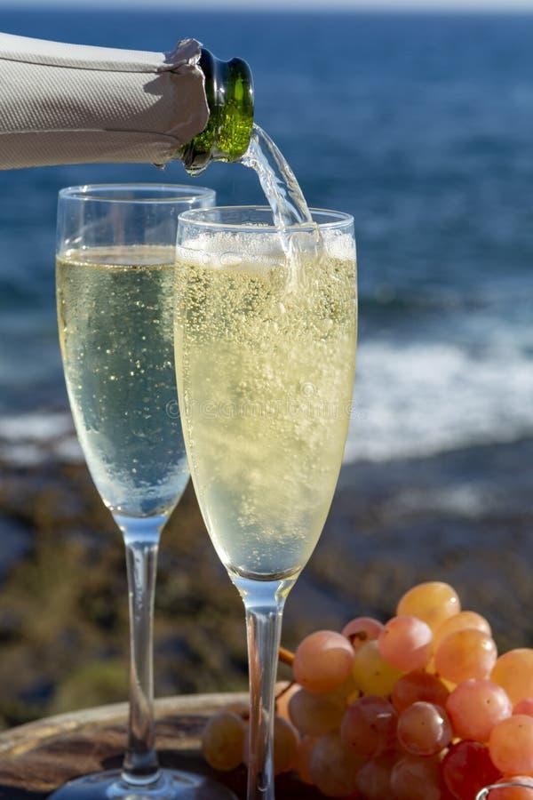 Serveur versant Champagne, prosecco ou cave en deux verres sur la terrasse ext?rieure avec la vue de mer photo stock