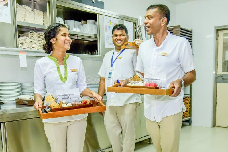 Serveurs et équipe de serveuse souriant avec des plateaux pleins des plats dans la cuisine image stock