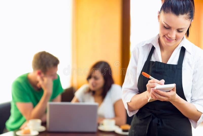 Serveuse écrivant un ordre avec des étudiants à l'aide de l'ordinateur portable au café photo libre de droits