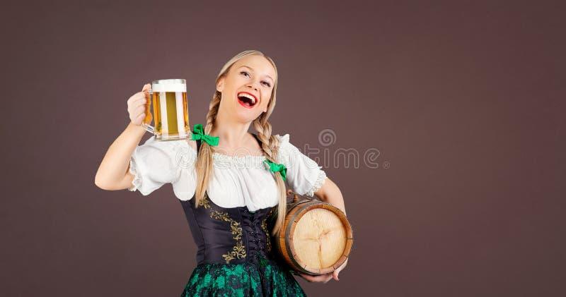 Serveuse de fille oktoberfest dans le costume national avec une tasse de bière photographie stock libre de droits