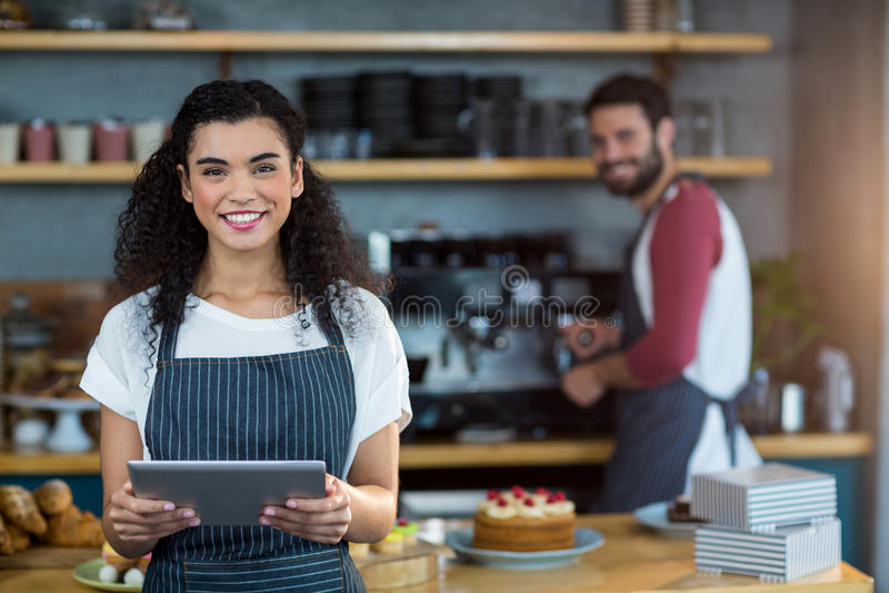 Serveuse de sourire à l'aide du comprimé numérique au compteur dans le café photos libres de droits