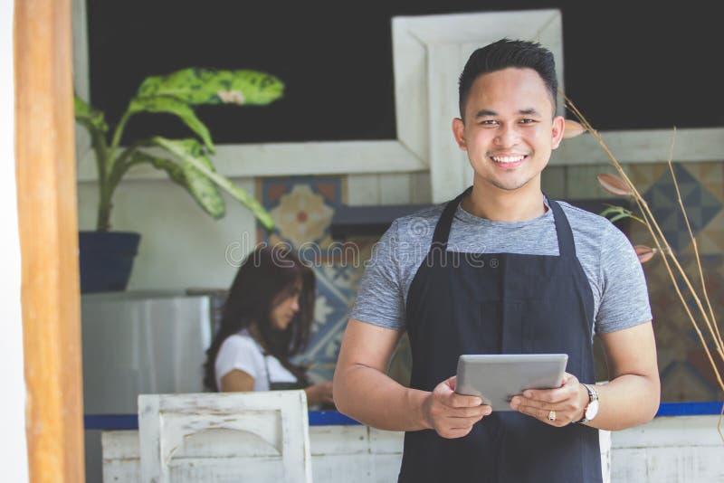 Serveuse masculine à l'aide du comprimé numérique en café photos libres de droits