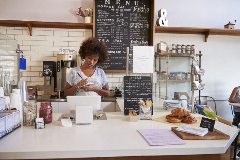 Serveuse notant un ordre au compteur du café image stock