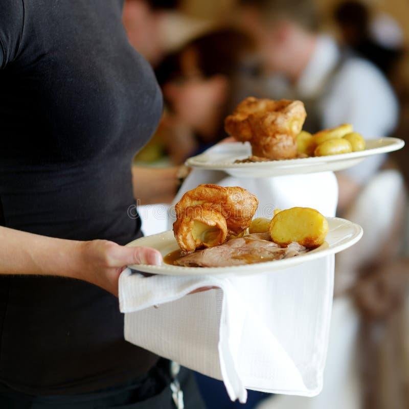 Serveuse portant deux plats avec le plat de viande image libre de droits