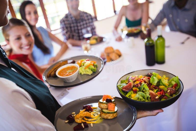 Serveuse tenant la nourriture du plat dans le restaurant photographie stock libre de droits