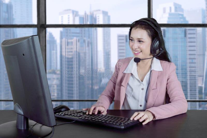 Serviço ao cliente bonito que trabalha com computador imagens de stock
