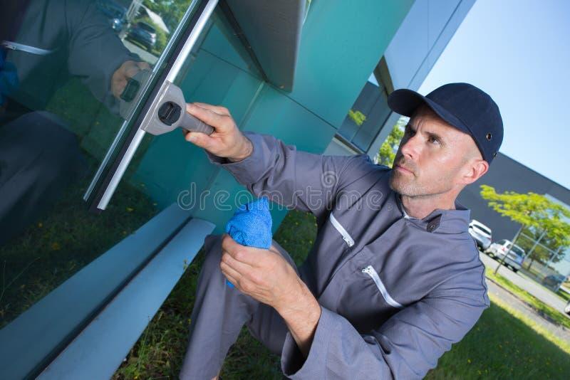 serviço das janelas da limpeza do trabalhador na construção alta da elevação fotos de stock