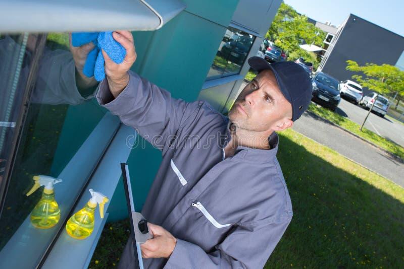 serviço das janelas da limpeza do trabalhador na construção alta da elevação imagem de stock