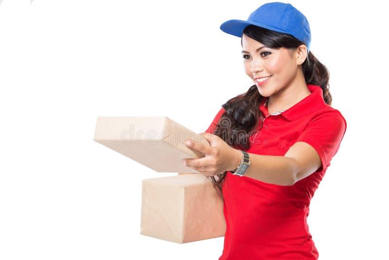 Serviço de entrega fêmea que entrega felizmente o pacote ao traje fotografia de stock royalty free