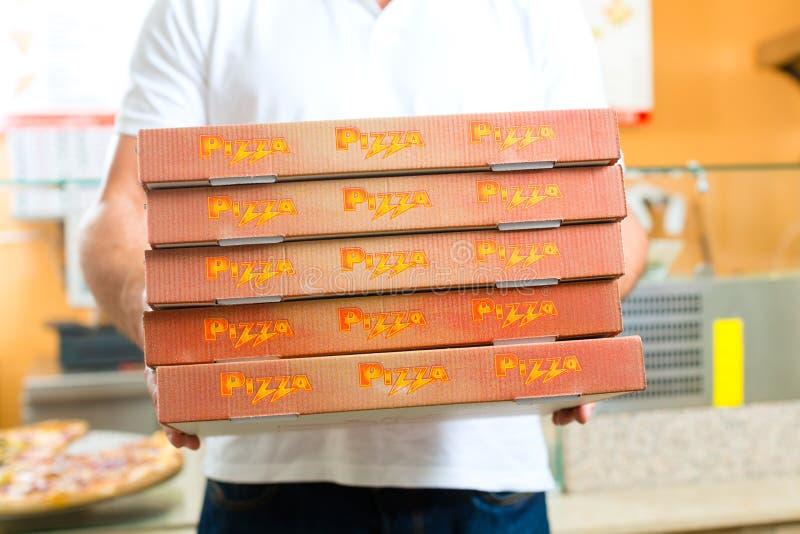Serviço de entrega - homem que guardara caixas da pizza foto de stock