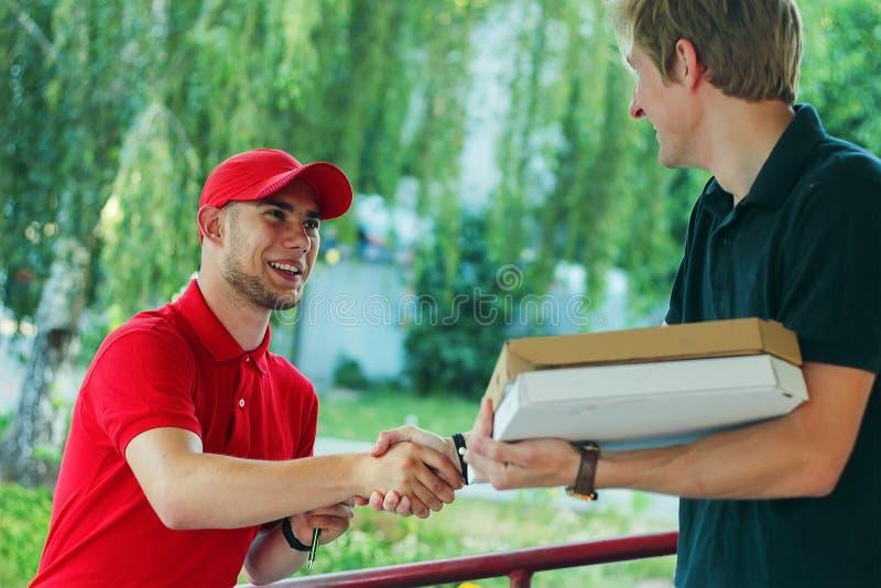 Serviço de entrega rápido que agita a mão do cliente masculino imagens de stock