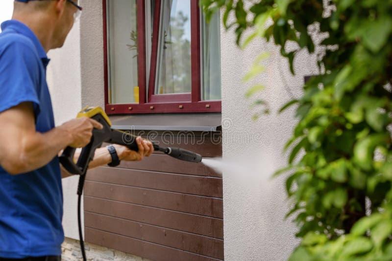 Serviço de limpeza da fachada da casa parede da lavagem do homem com arruela de alta pressão fotografia de stock