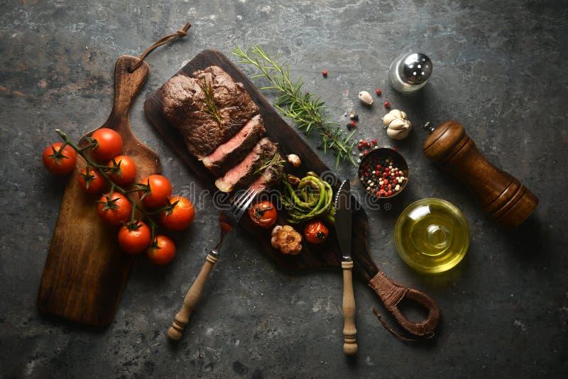 Serviço do bife da carne na placa de carniceiro de madeira com os vários ingredientes que cercam, com forquilha e faca vista supe foto de stock