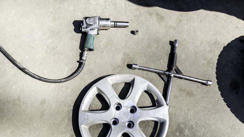 Serviço do carro, porca do dispositivo bonde de uma roda do carro em um fundo branco, imagem de stock