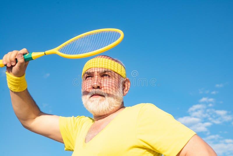 Serviço do jogador de tênis do homem superior Conceito da aposentadoria da liberdade O homem superior está apreciando o estilo de imagens de stock royalty free