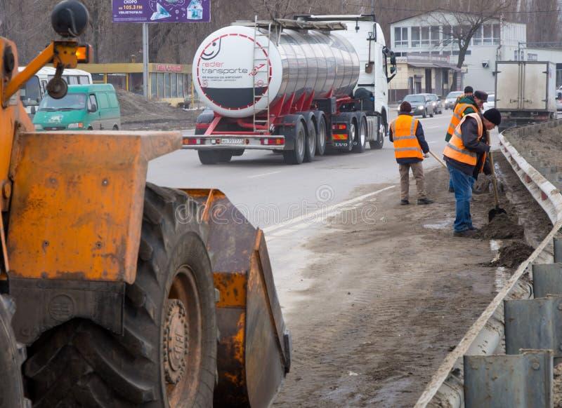 Serviço rodoviário limpa a areia do lado da estrada após o inverno imagens de stock royalty free
