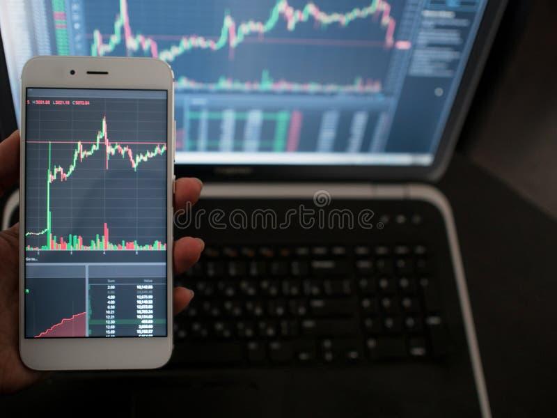 serviços da Cruz-plataforma para trocar na troca Mão com o telefone no fundo de um portátil imagens de stock royalty free