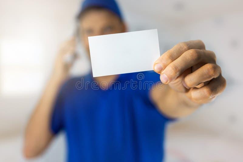 Serviços para o Handyman - trabalhador que mostra um cartão de visita em branco e faz uma chamada telefônica imagem de stock royalty free