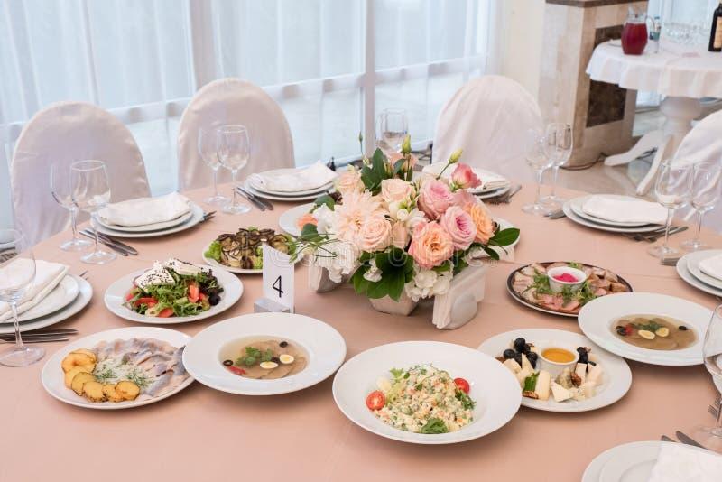 Servi à la table de restaurant de banquet avec des plats, casse-croûte, couverts photographie stock libre de droits
