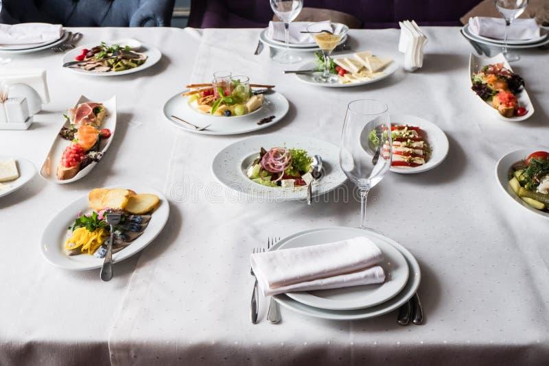 Servi à la table de restaurant de banquet avec des plats, casse-croûte, couverts, verres photos stock