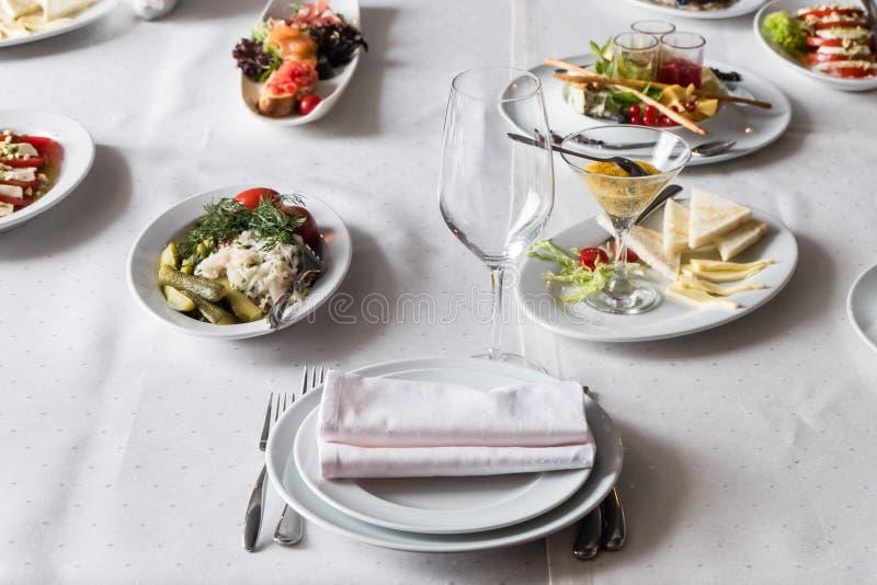 Servi à la table de restaurant de banquet avec des plats, casse-croûte, couverts, vin photographie stock libre de droits