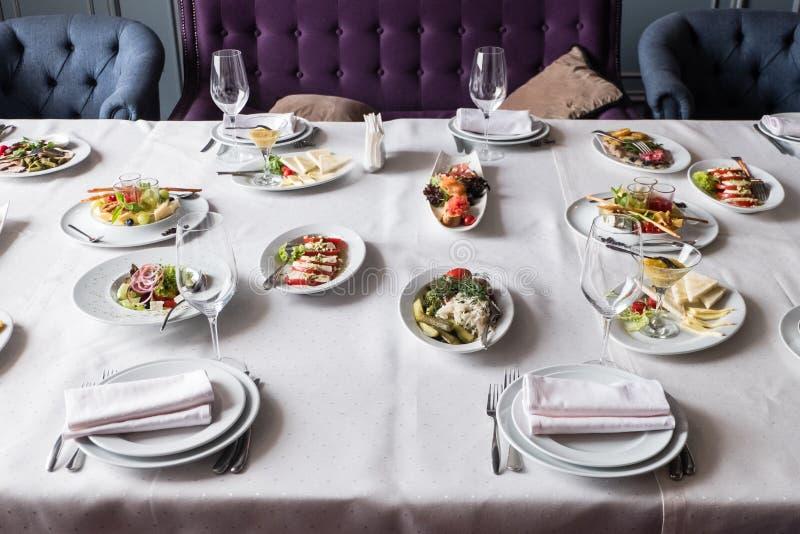 Servi à la table de restaurant de banquet avec des verres de plats, de casse-croûte, de couverts, de vin et d'eau, nourriture eur images libres de droits