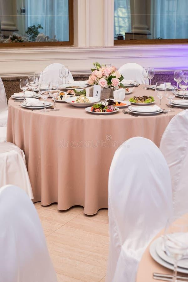 Servi ? la table de restaurant de banquet avec des verres de plats, de casse-cro?te, de couverts, de vin et d'eau, nourriture eur image stock
