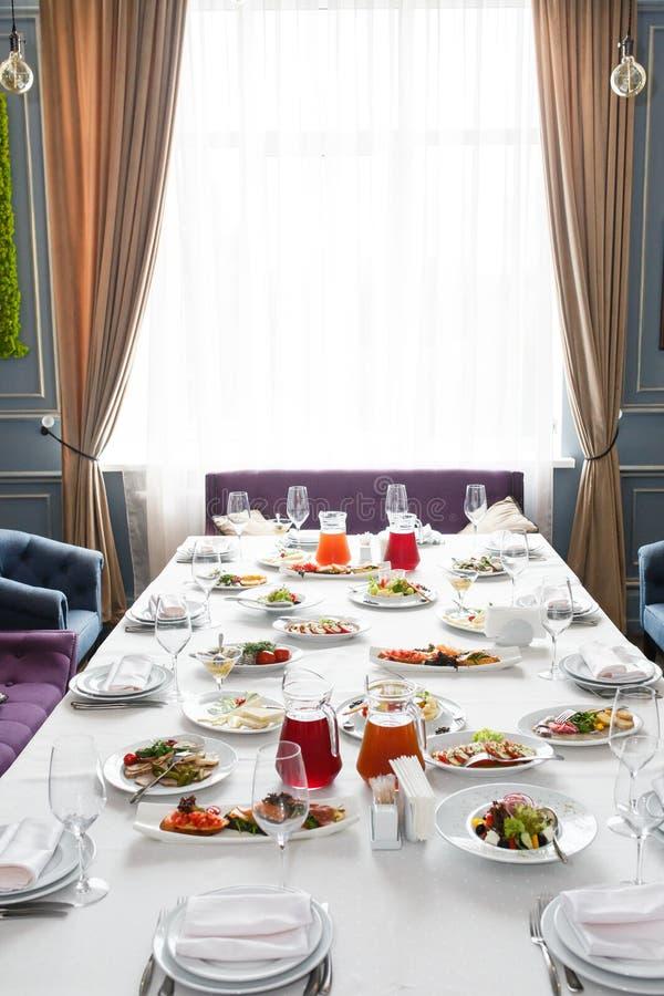Servi ? la table de restaurant de banquet avec des verres de plats, de casse-cro?te, de couverts, de vin et d'eau, nourriture eur photographie stock libre de droits